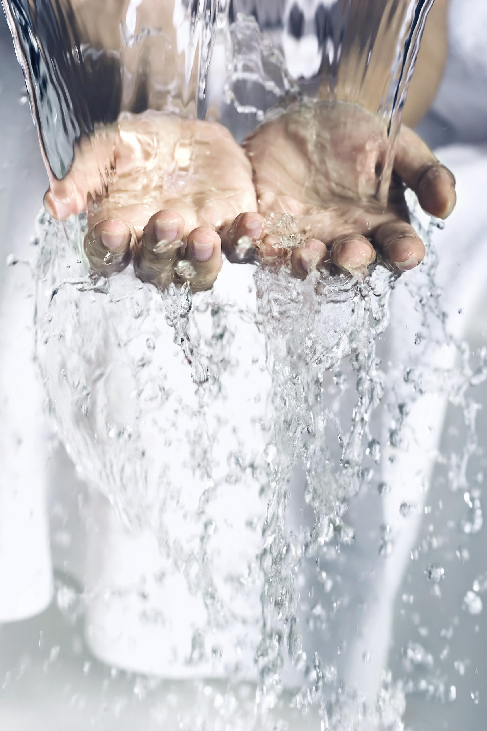 Water cascading over a pair of hands.