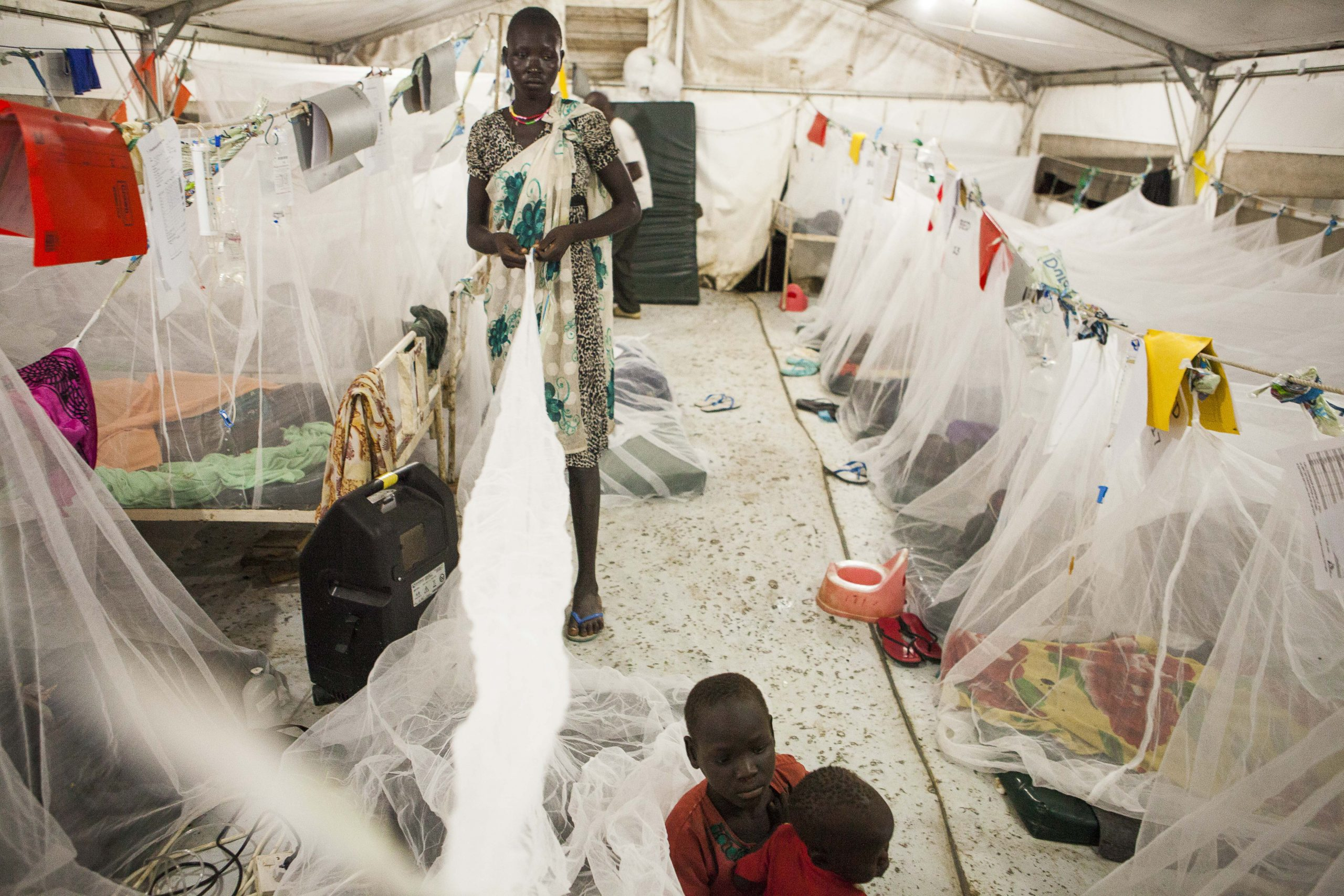 A family arrives at the middle of the night and prepares a bednet and mattress on the floor in the crowded hospital at Bentiu POC. Photo by Brendan Bannon. September 2015. Bentiu, South Sudan
